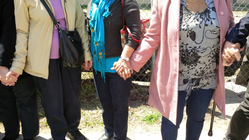 Former staff and Grace Hospital alumni hold hands as part of a final goodbye to the old building.