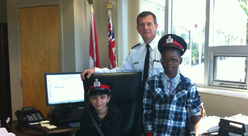 Stephanie Figueiredo (left) and Max Uhuangho pose with Chatham-Kent Police Chief Dennis Poole.