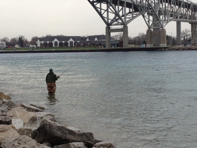 A fisherman waits for his big catch beneath the Bluewater Bridge's in Pt. Edward. BlackburnNews.com File Photo