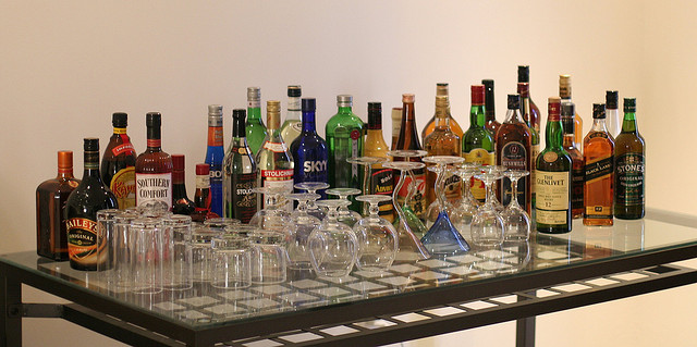 array of liquor bottles and glasses ready for a party