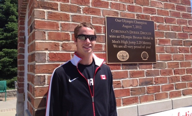 Derek Drouin poses beside a plaque erected in his honour in Corunna recognizing his bronze medal win in 2012 (BlackburnNews.com file photo)
