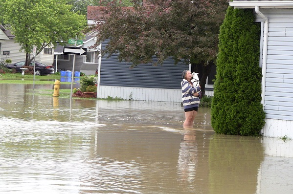 Young woman standing in the flood waters at Lucier Estates in McGregor.
