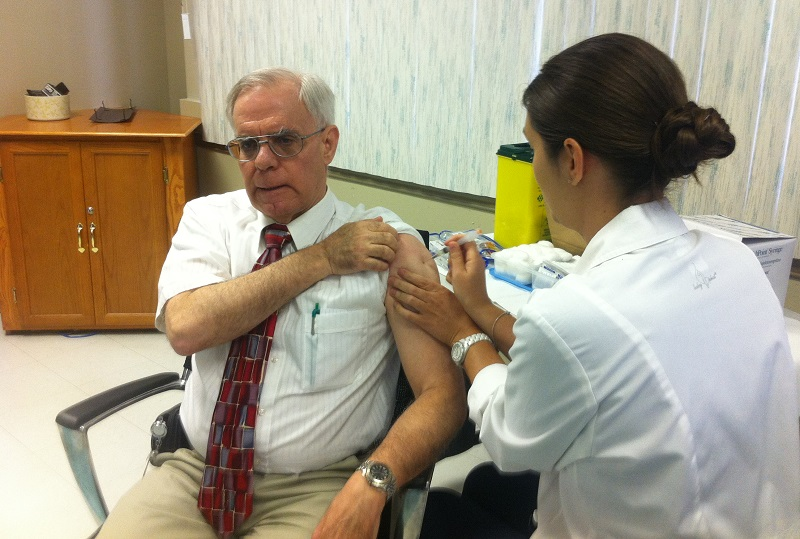 Retired Medical Officer of Health Dr. Allen Heimann receiving his 2013 flu shot.
