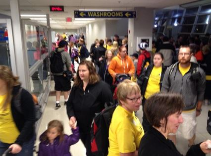 families going through security at London International Airport