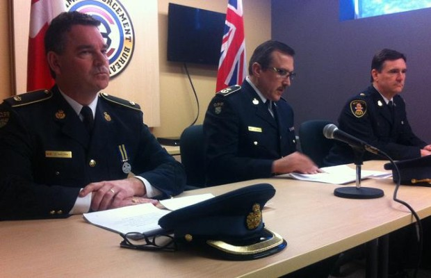 OPP Detective Inspector Greg Watson (left), OPP Deputy Commissioner Scott Tod (centre), and Windsor Police Service Superintendent John St. Louis (right), speak to the media at the OPP's Essex detachment, March 7, 2014.