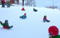 several children sliding down a snowy hill