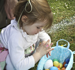 little girl checking her colourful Easter eggs in a basket