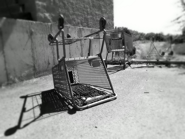turned-over shopping carts abandoned on a cement pad