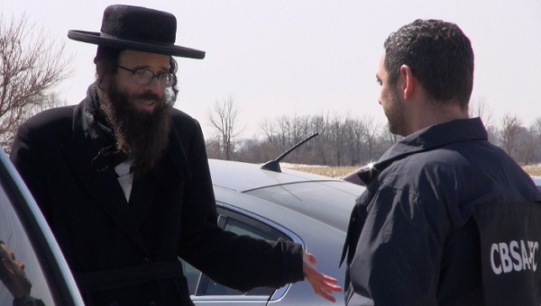 A member of the Lev Tahor community pleads with a Canadian Border Services Agency Officer. Photo taken on April 2, 2014 by Ashton Patis.