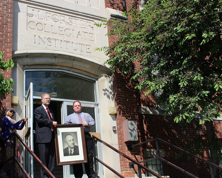 Principal David Garlick and Vice Principal Scott Braithwaite hold a picture of J.L Forster on the steps of the secondary school closing in June.