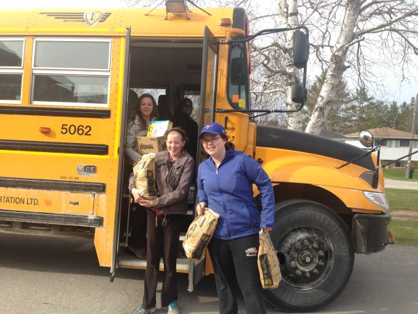 Wingham Sacred Heart Students load donated food into school bus for 'Stuff That Bus ' event. (BlackburnNews.com file photo)