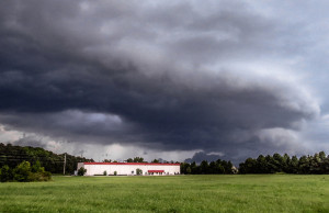 storm clouds gather over a rural building