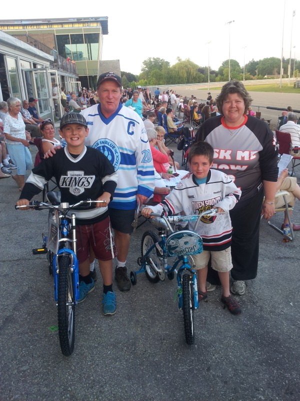 picture is of bicycle winners  Corey Lacey of Walkerton and Gabriel Yeoman of Shallow Lake receiving their prize from MC Fred Wallace, and raceway hostess Lisa Rumble.