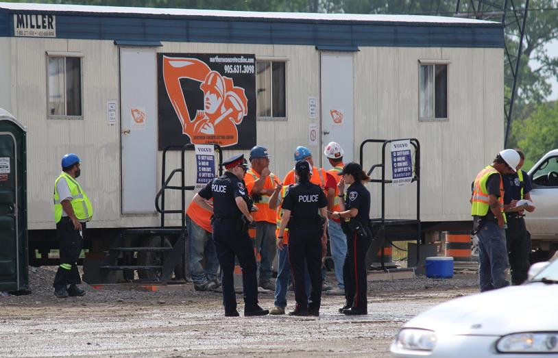 Windsor police officers talk to Herb Gray Pkwy. construction workers after a fatal industrial accident at the site along Huron Church Rd. at Labelle St., June 17, 2014. (photo by Mike Vlasveld)