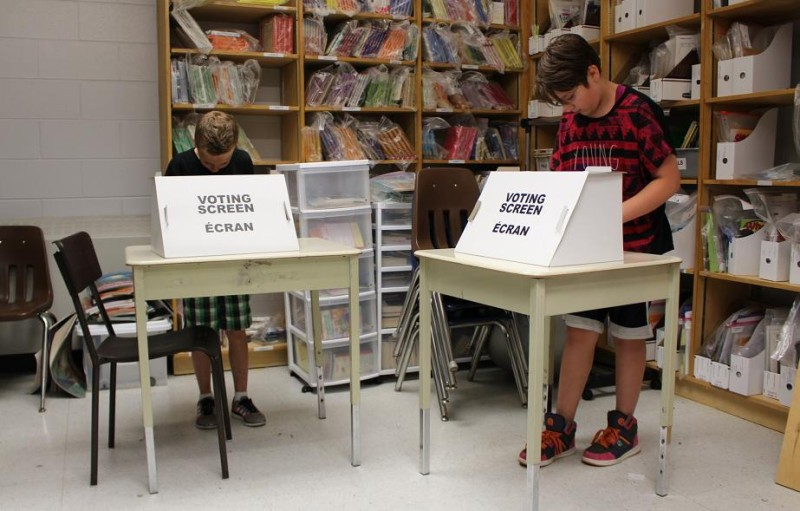Grade six students Matteo Asta (left) and Molly Campbell (right) at St. Angela Catholic Elementary School take part in Ontario's Student Vote, June 11, 2014. (photo by Mike Vlasveld)
