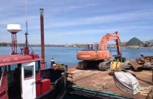 An excavator being used for shoreline restoration work sits on a barge near Sarnia's government dock . BlackburnNews.com File Photo (Taken by Melanie Irwin)