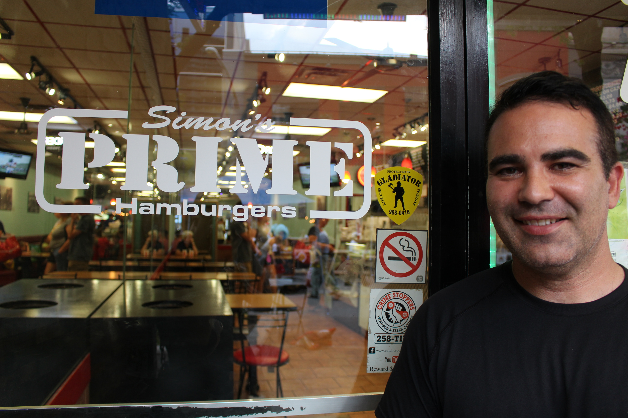 Simon Protopapas, owner of Simon's Prime Hamburgers, stands out front of his bruger joint in downtown Windsor on Ouellette Ave. on August 16, 2014. (Photo by Ricardo Veneza)