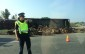 An OPP officer stands near a tractor trailer that rolled on the ramp from Veterans Memorial Parkway to the eastbound 401.