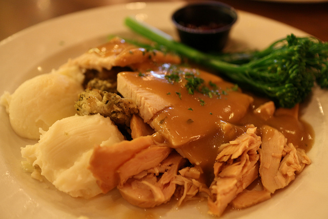 plate with mashed potatoes, turkey, broccoli and gravy on it