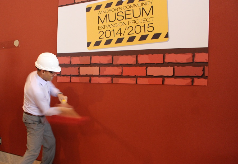 Windsor Mayor Eddie Francis takes a swing at a wall to kick off the museum expansion project at 401 Riverside Dr. West. (Photo by Maureen Revait)