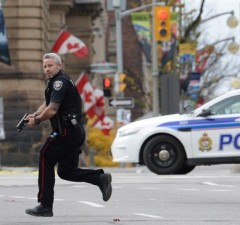 An Ottawa police officer runs with his weapon drawn in Ottawa on Wednesday Oct.22, 2014.Police are expanding a security perimeter in the heart of the national capital after a gunman opened fire and wounded a soldier at the National War Memorial before injuring a security guard on Parliament Hill, where he was reportedly shot dead by Parliament's sergeant-at-arms. THE CANADIAN PRESS/Sean Kilpatrick