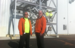 Production Manager Rick Smeenk (left) and Pioneer Integrated Operations Director Bryce Eger (right), join workers outside the new blending and treating facility.
