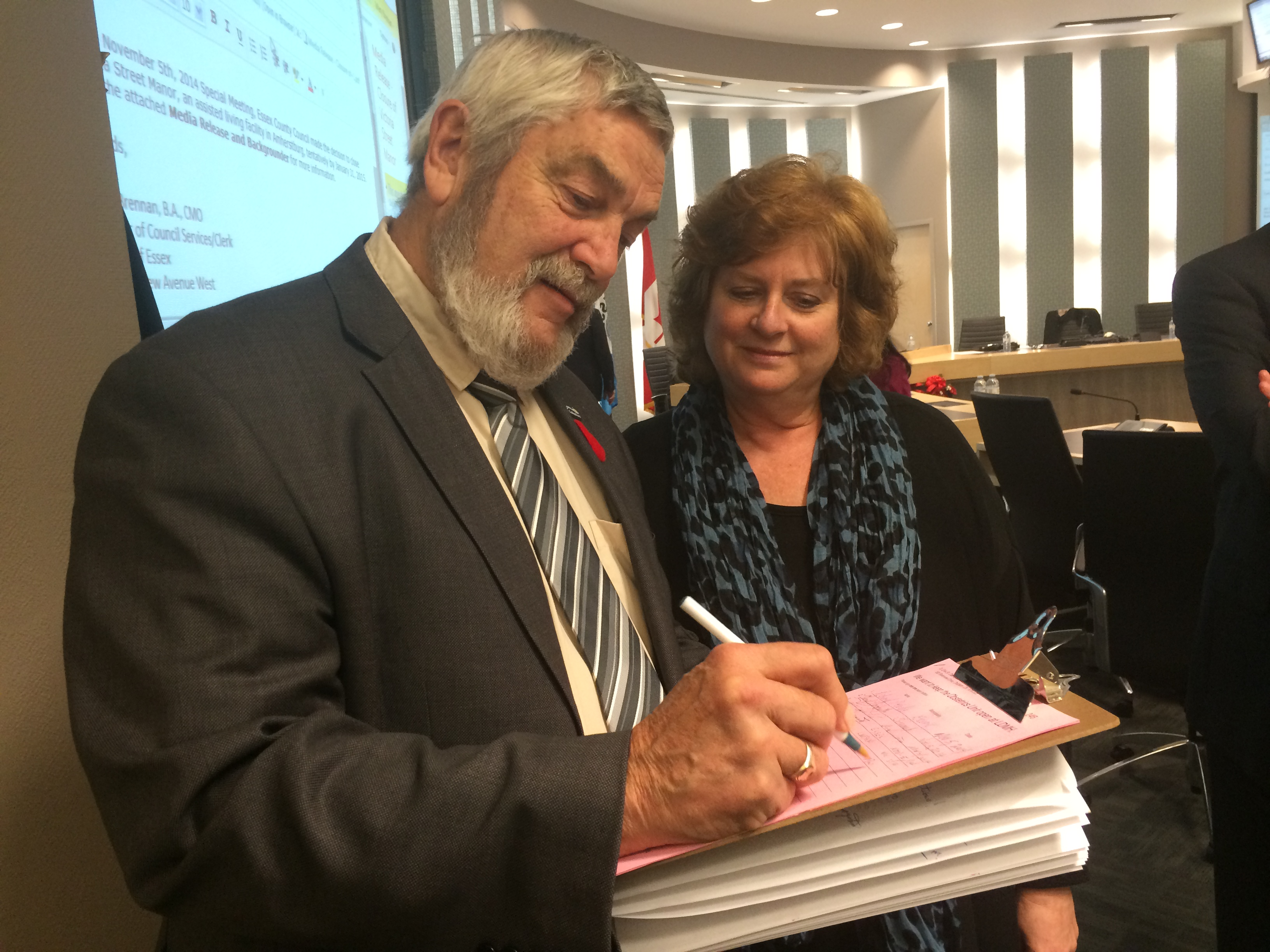 Lakeshore Mayor Tom Bain (L) in Council Chambers at the Essex Civic Centre on November 5, 2014 signing a petition handed out by former Kingsville Deputy Mayor Tamara Stomp (R) opposing the pending closure of the obstetrics ward at Leamington District Memorial Hospital. (Photo by Ricardo Veneza)