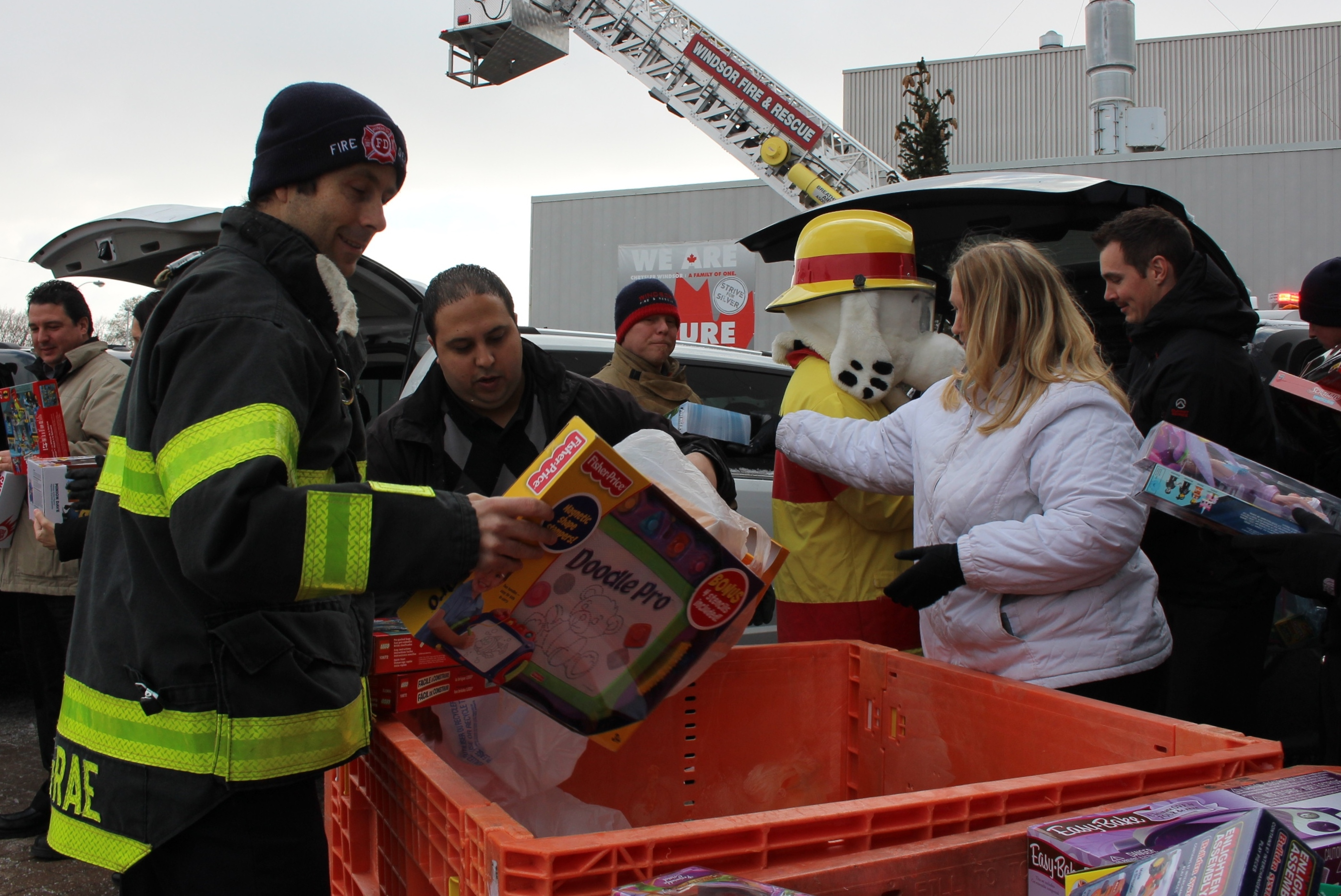 Windsor firefighter John McRae and the rest of his crew collect toys from Chrysler, being donated to Sparky's Toy Drive, November 20, 2014. (photo by Mike Vlasveld)