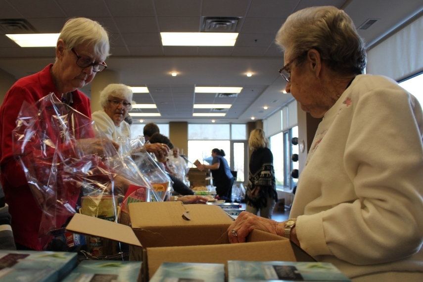 Amica Helping Hands donation baskets being assembled by residents and staff at the Riverside Dr. E. location, December 4, 2014. (photo by Mike Vlasveld)