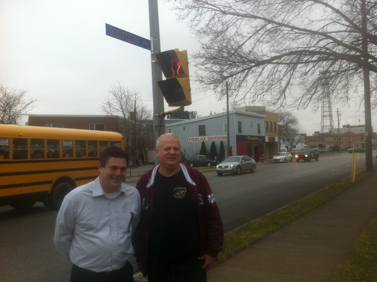 Councillor Derek Robertson and Chatham Goodfellows President Scott Williston stand in front of the Goodfellow Way sign that replaces Wellington Street for December.