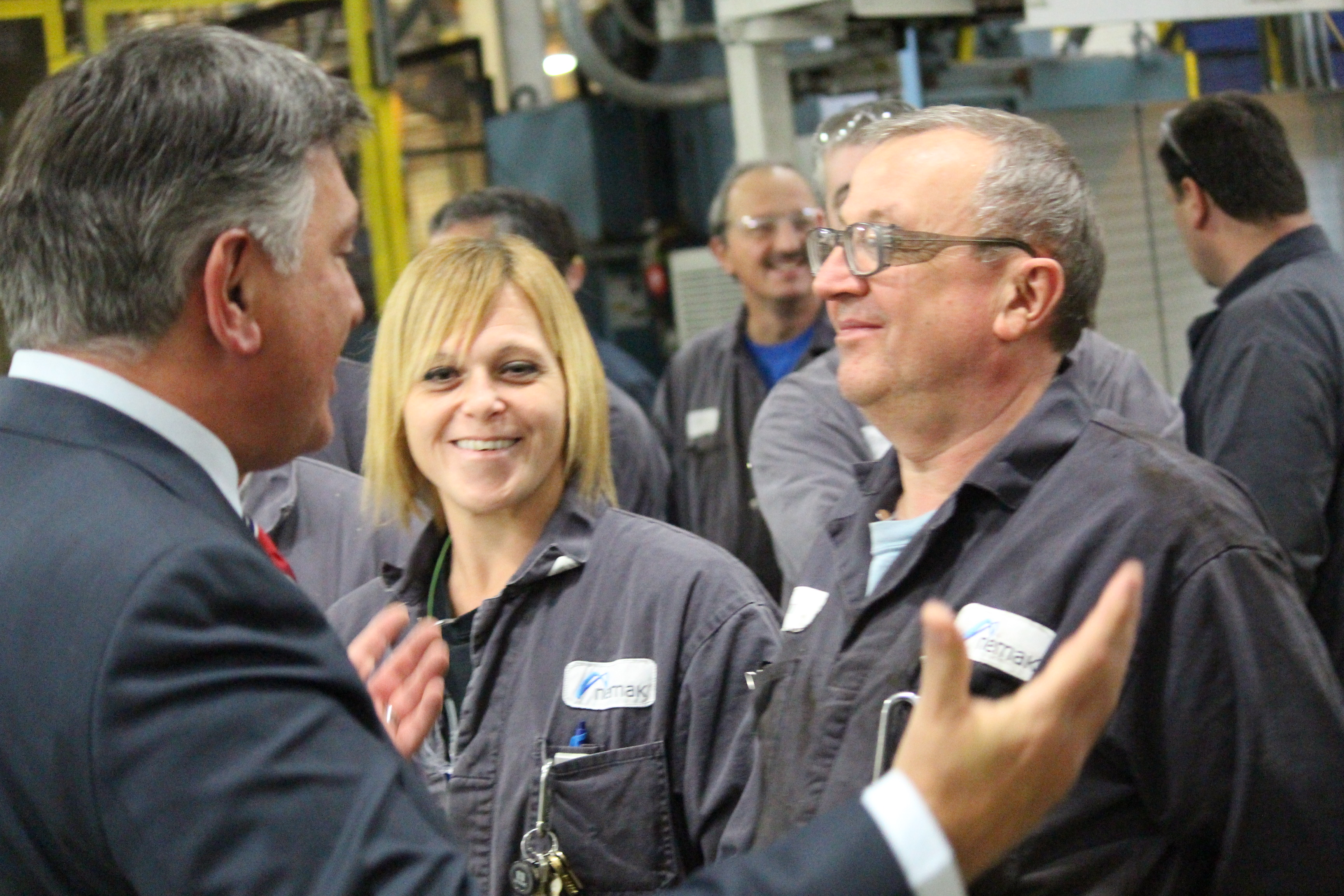Ontario Finance Minister Charles Sousa, left, speaks with Nemak workers after announcing a $1.5-million government grant for the plant. (Photo by Jason Viau)