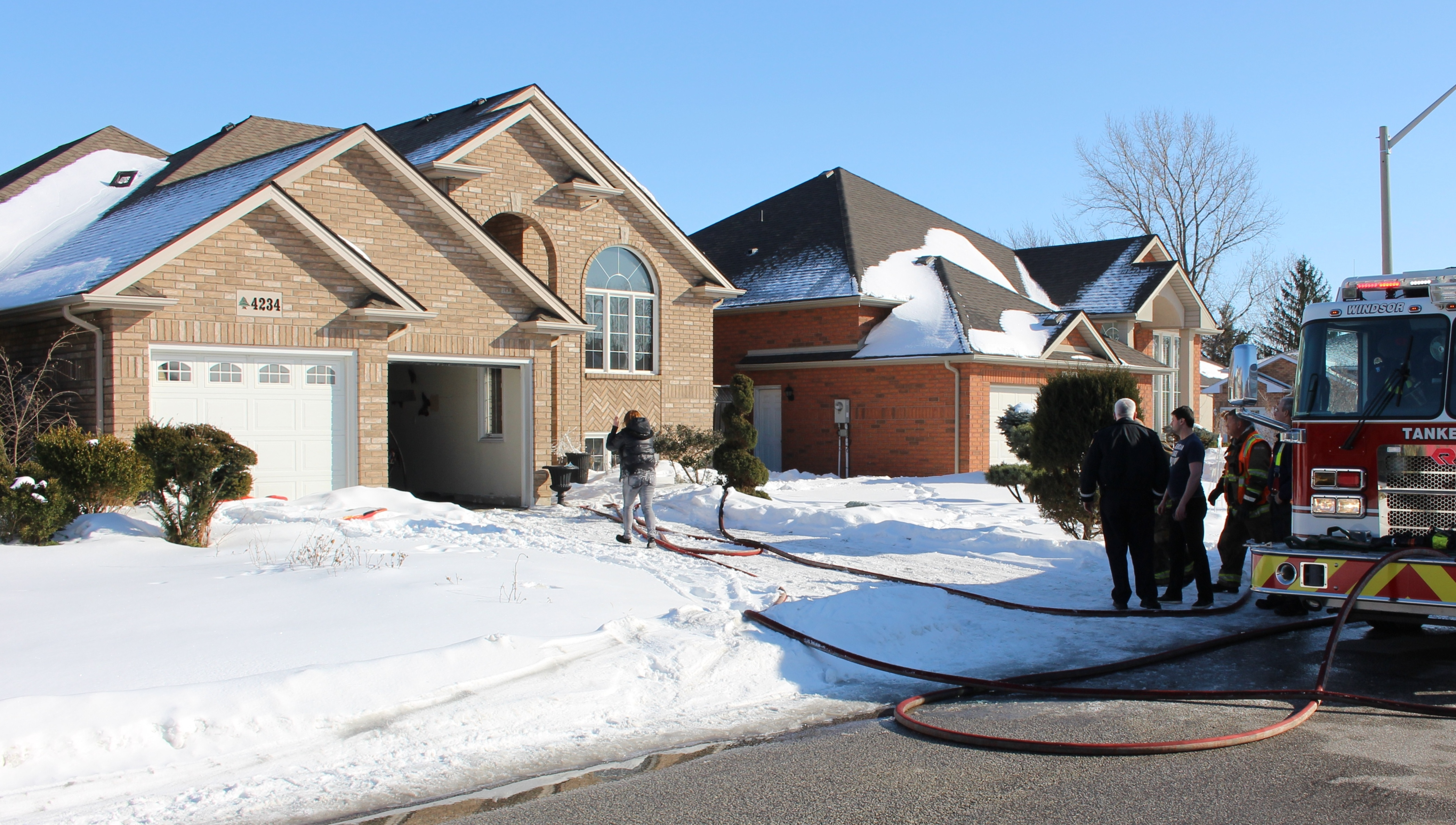 Homeowners return to the scene of a blaze in the 4200-block of Barton Cres., February 23, 2015. (Photo by Mike Vlasveld)