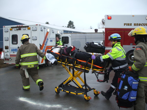Meaford firefighters and EMS staff pull a gurney bearing one of the two 'victims' of a head-on collision to a waiting ambulance. (Photo: James Armstrong)