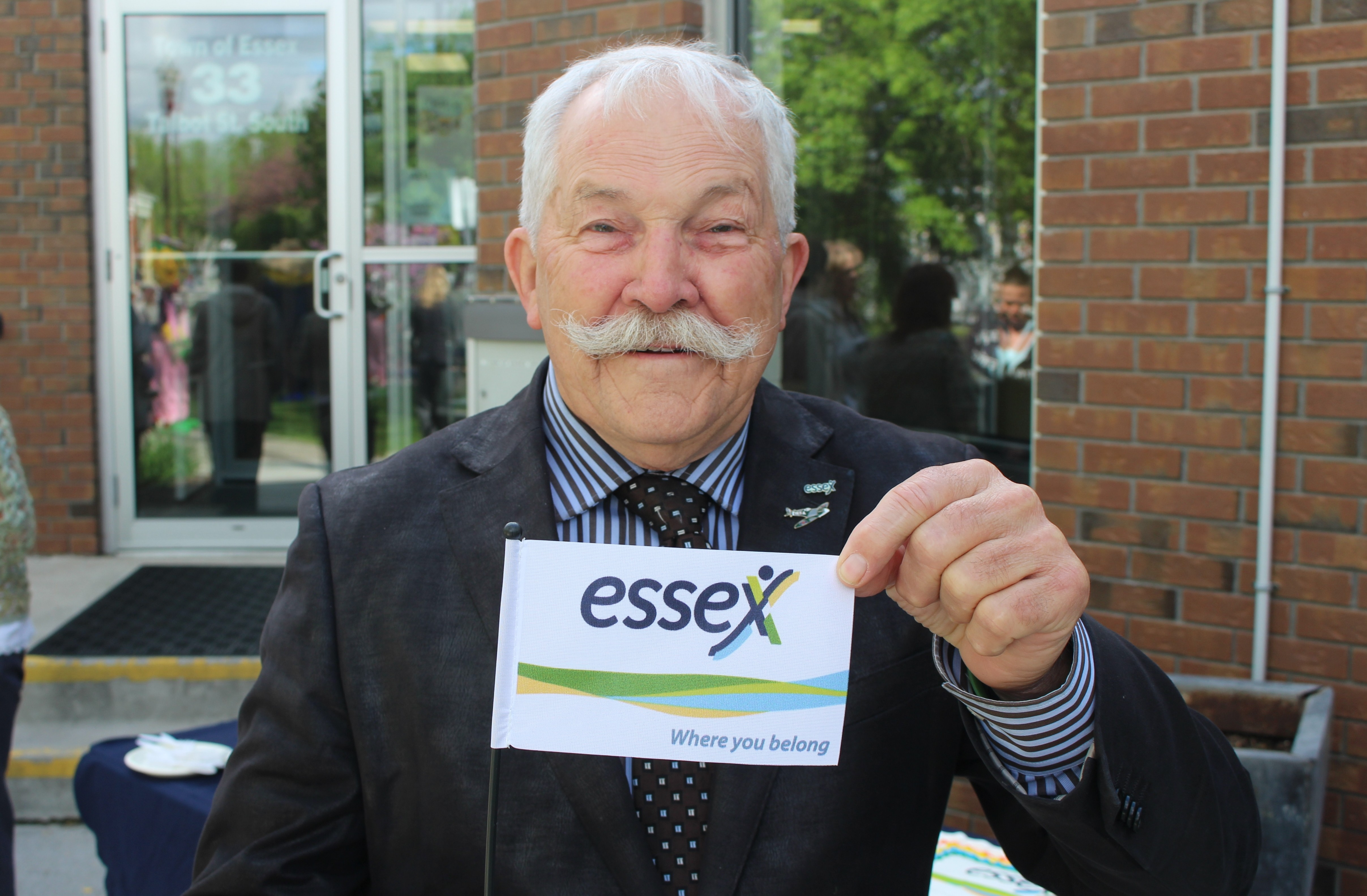 Essex Mayor Ron McDermott holds up a mini version of his towns new flag, May 13, 2015. (Photo by Mike Vlasveld)