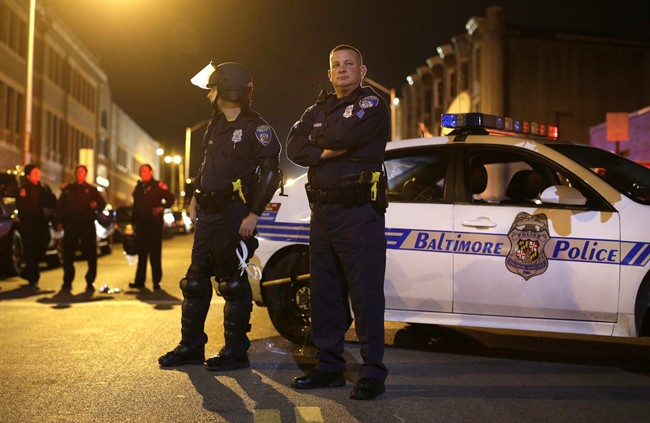 Members of the Baltimore Police Department wait for curfew to begin for the third night, Thursday, April 30, 2015, in Baltimore. (AP Photo/Patrick Semansky)