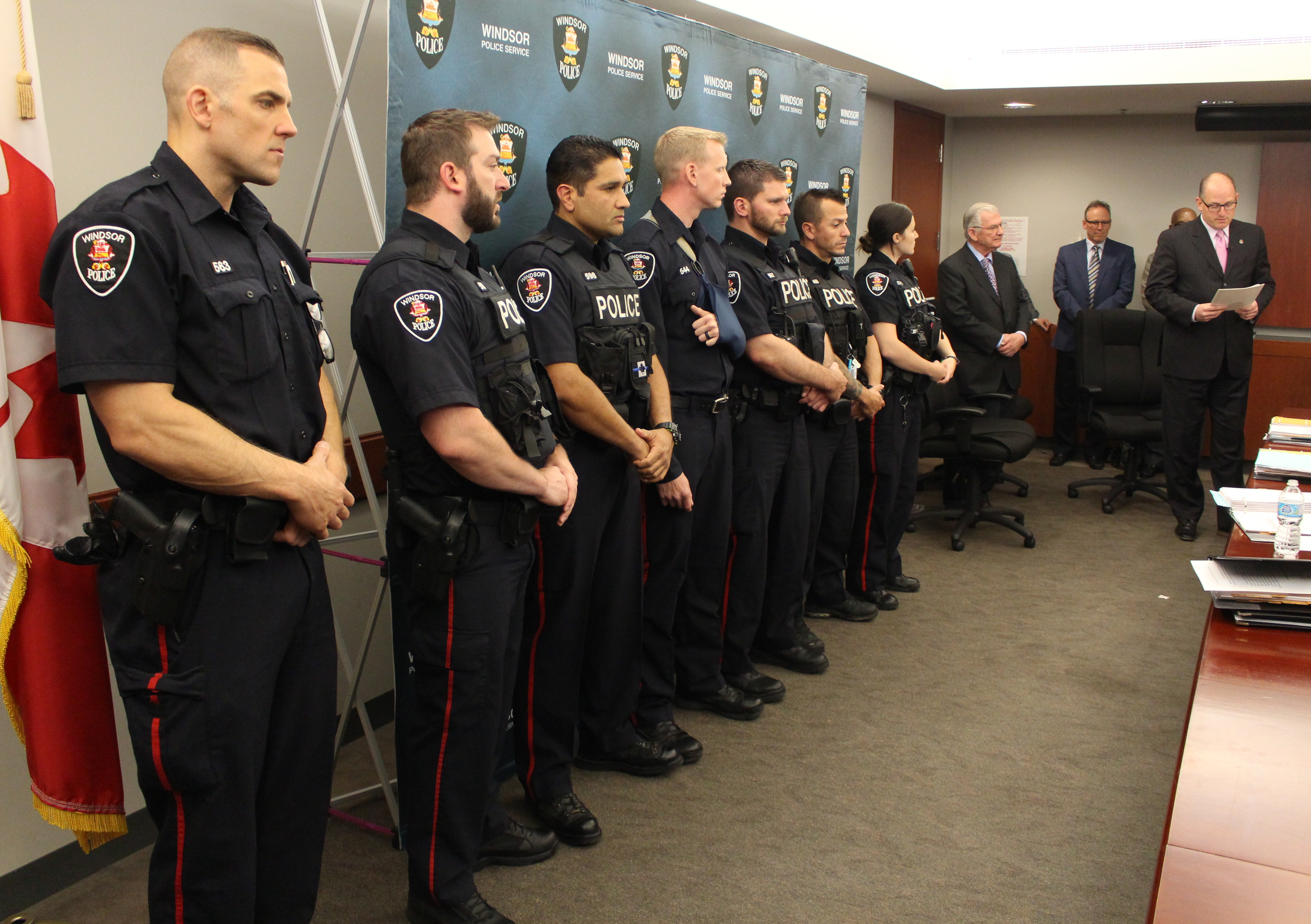 Windsor Mayor Drew Dilkens (far right) publicly recognizes seven Windsor police officers at a Windsor Police Board meeting, June 2, 2015. (Photo by Mike Vlasveld)
