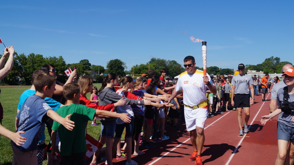 Torchbearer Joel Skinner finishes up the Sarnia Pan Am Games torch run June 16, 2015 (BlackburnNews.com Photo by Briana Carnegie)