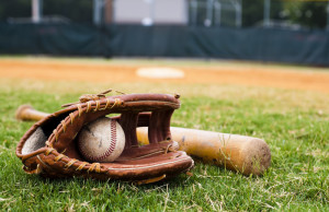 Old baseball, glove, and bat on field with base and outfield in background. © Can Stock Photo Inc. / dehooks
