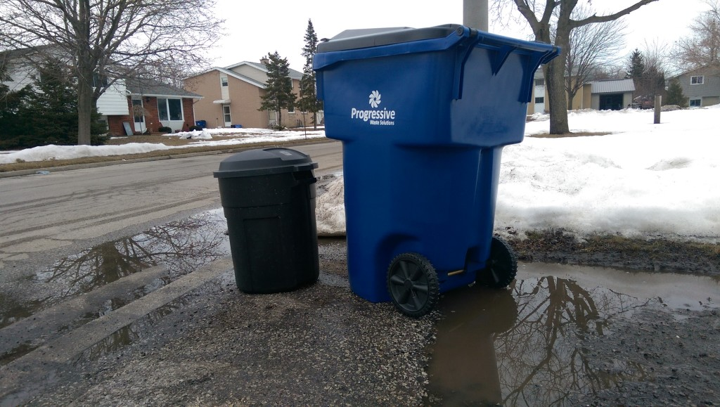 A Progressive Waste Solutions garbage toter (right) stands beside a standard garbage pail. March 15, 2015. (Photo by Matt Weverink)