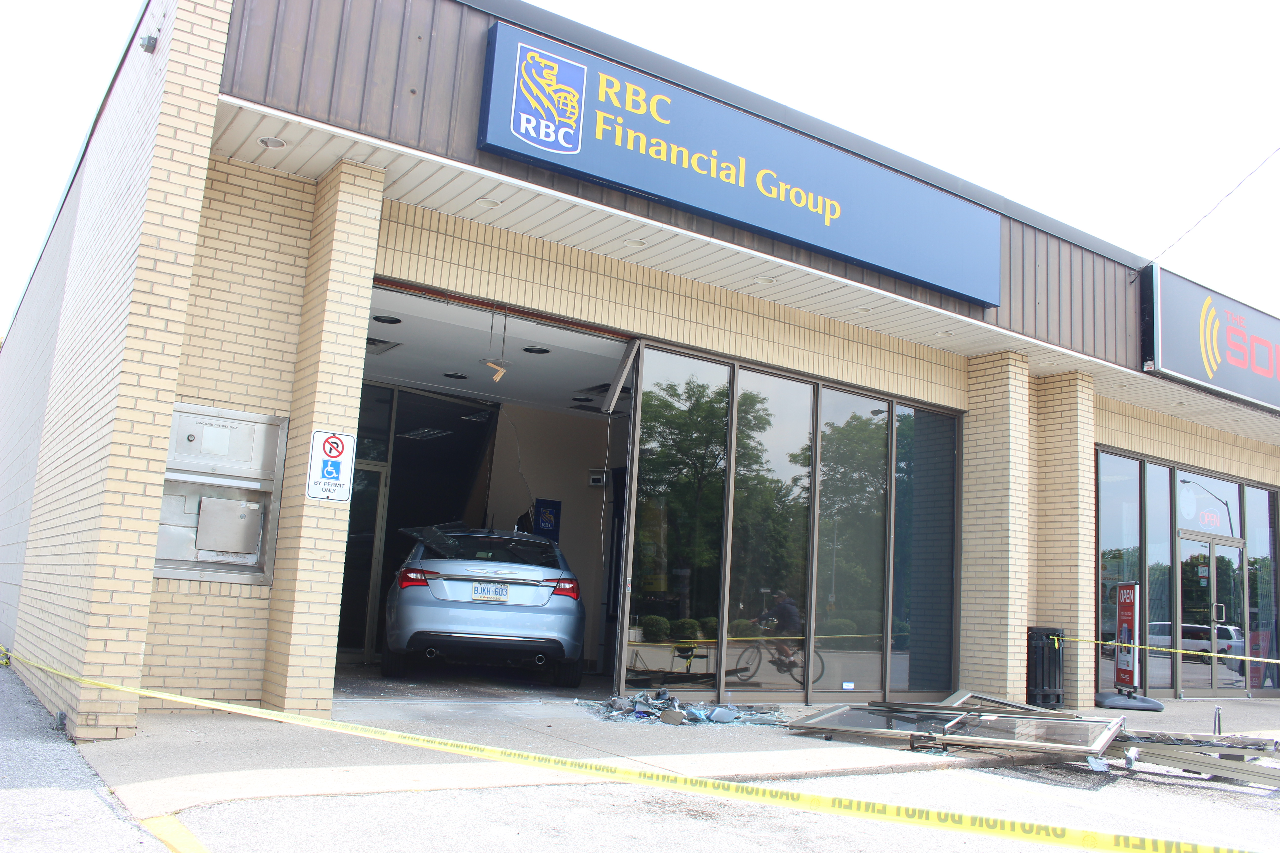 Three people were sent to hospital after a car smashes through the front of an RBC Bank on Huron Church Rd., July 3, 2015. (Photo by Jason Viau)