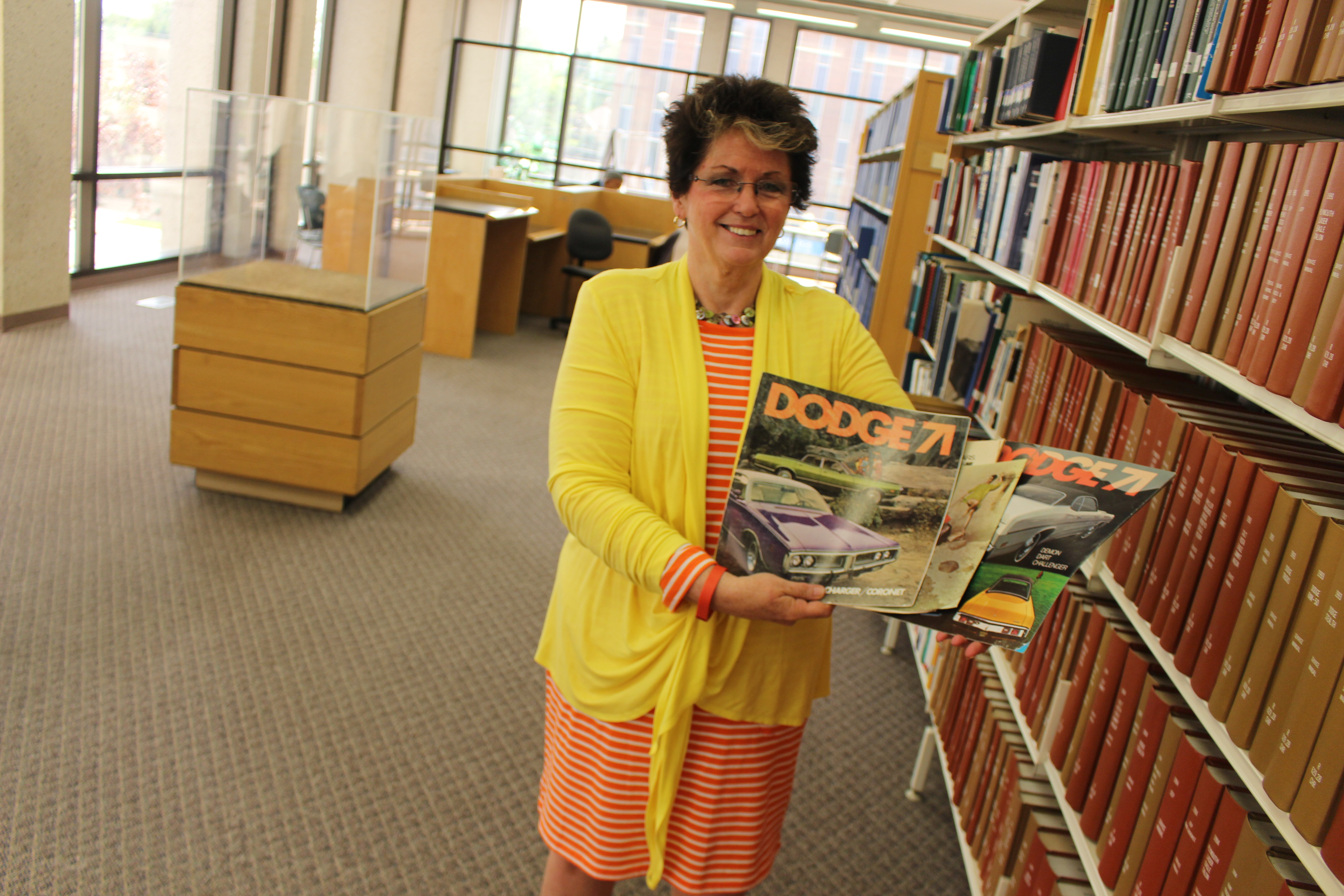 Windsor Public Library CEO Kitty Pope holds some material that will be on display at the new automotive exhibit, July 23, 2015. (Photo by Jason Viau)