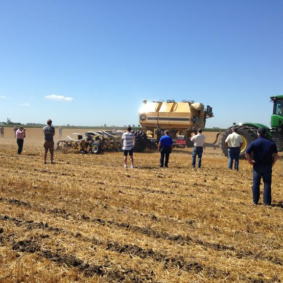 Farmers watch a demonstration of strip tillage equipment July 30, 2015 (Photo by Simon Crouch)