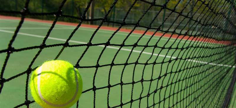 Tennis ball hits net. © Can Stock Photo Inc. / mflippo