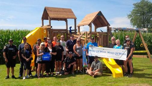 Volunteers pose in front of Michael's playset. (Photo courtesy of Chatham-Kent police)