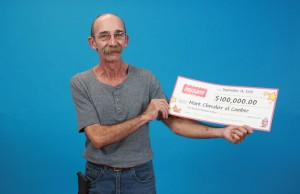 Mark Chevalier holds up a cheque after winning $100,000 with an Instant Extreme Millions scratch ticket. (Photo courtesy of the OLG)