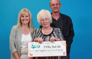 Jane Tiggelaar, Terence Tiggelaar and Laurie Fach hold up their LOTTO MAX lottery winnings. (Photo courtesy of the OLG)