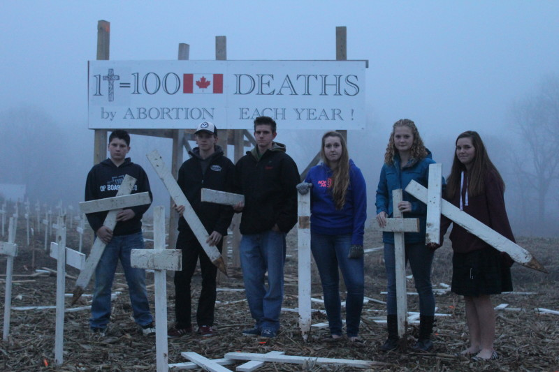 Members of the Eben-Ezer Canadian Reform Church youth group stand at their vandalized Pro LIfe display on Longwoods Rd., December 7, 2015 (Photo by Jake Kislinsky)