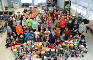 Grade 6 students at Our Lady of Mount Carmel School and OPP Constable Raquel Otterman collect donations for children in northern Ontario. (Photo courtesy the OPP)