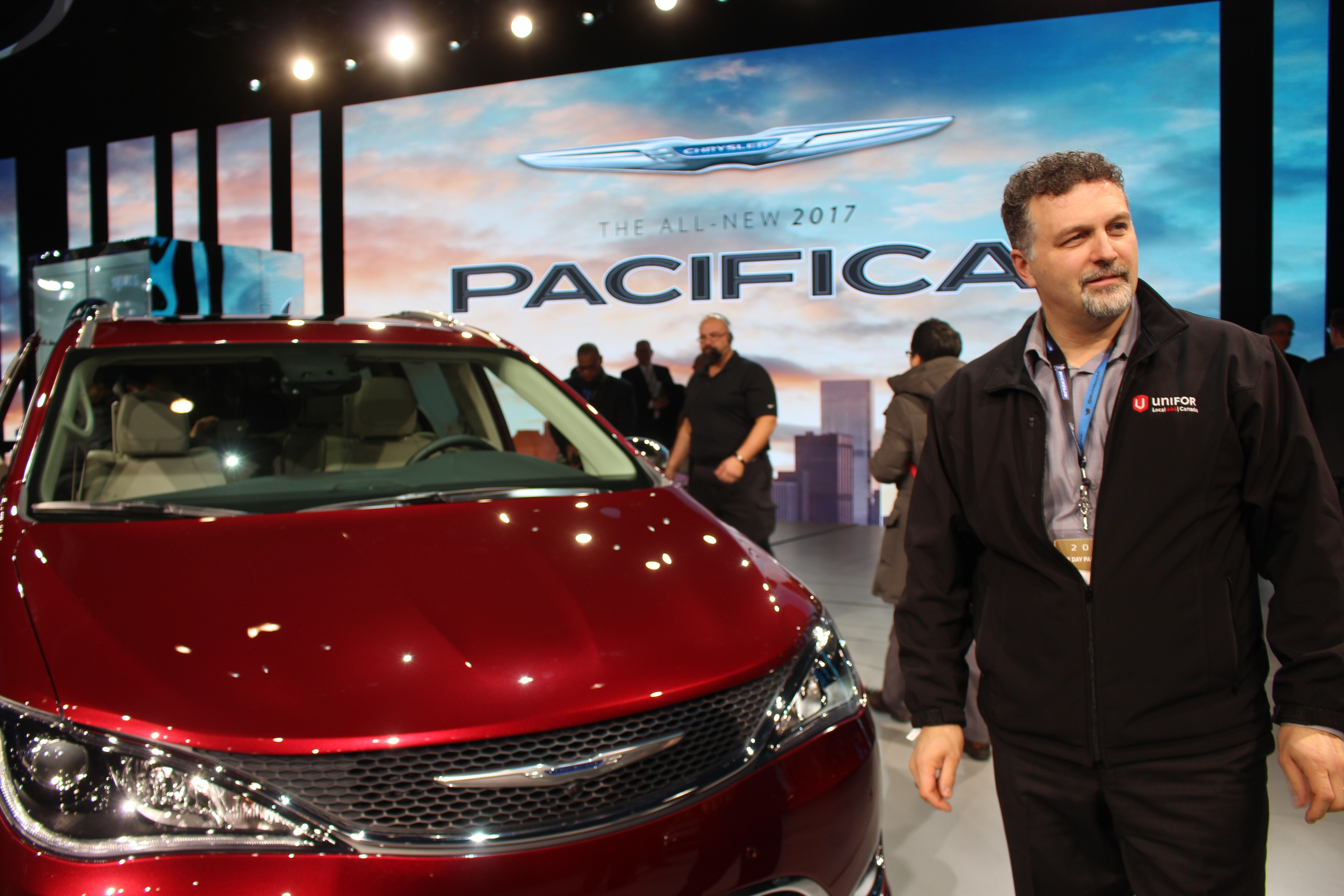Unifor President Dino Chiodo poses with he Chrysler Pacifica unveiled at the North American International Auto Show 2016. (Photo by Maureen Revait)