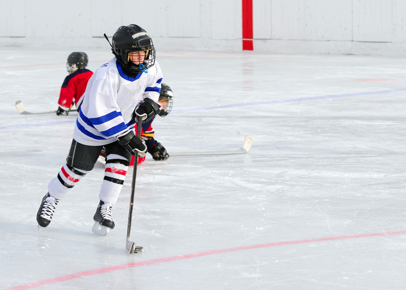 Young hockey player with the puck. © Can Stock Photo Inc. / Pixart